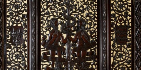 The carved headboard shows the arms of England, France and the King and Queen depicted as Adam and Eve