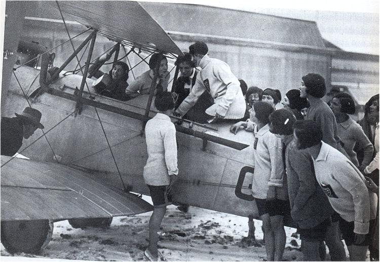 Mary demonstrating the controls of her aeroplane to a group of school girls